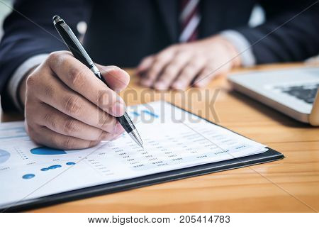 Professional businessman working Doing finance on laptop document graph and analysis business strategy to development profit.
