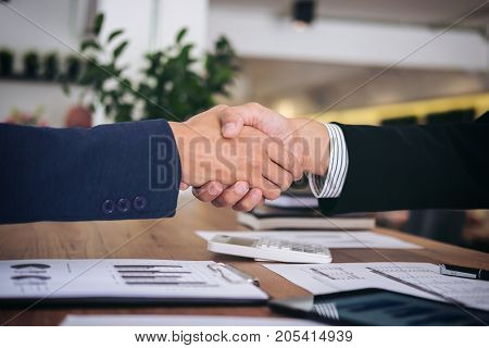 Two smiling businessman shaking hands together after good deal connection to join investment business.