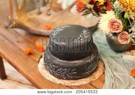 confection, decoration, holidays concept. on the celebration table there is ravishing wedding cake of extraordinary black colour with painted white elements of form of leaves on the sights