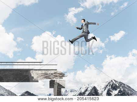 Businessman jumping over huge gap in concrete bridge as symbol of overcoming challenges. Skyscape and nature view on background. 3D rendering.
