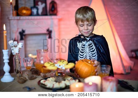 Happy cute blonde boy in skeleton costume with cape taking pumpkin from candy bar table while standing alone in decorated studio for parties