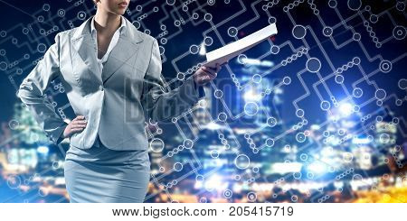Businesswoman wearing modern suit and holding contract or report in her hand