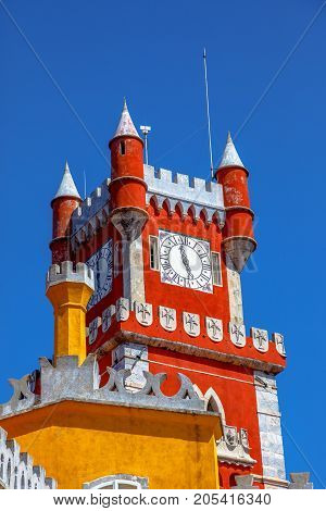 Detail of main red clock tower of Pena National Palace, in Portuguese Palacio da Pena, Sintra, near Lisbon, in a sunny day, blue sky. The palace is Unesco Heritage and one of Seven Wonders of Portugal