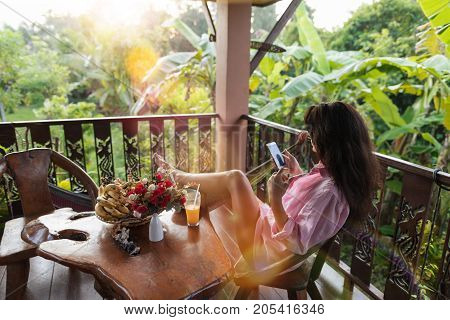 Young Woman Holding Cell Smart Phone On Terrace In Tropical Garden Back Rear View Of Beautiful Girl Enjoying Tropic Forest Landscape Messaging Online Social Media Communication Concept