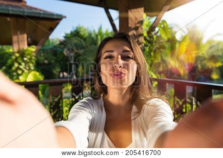 Pretty Woman Blowing Kiss Taking Selfie Photo Young Girl Make Self Portrait Outdoors Over Natural Background