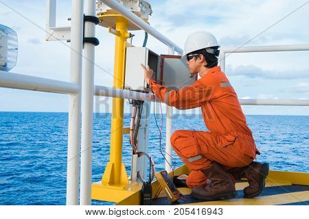 Electrical and Instrument Technician is inspection on lighting of navigation aid system at oil and gas wellhead remote platform Inspector work.