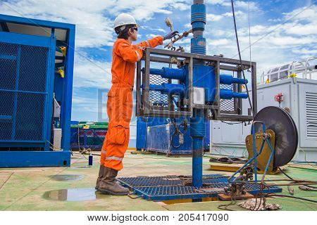 Offshore oil and gas industry oil rig worker inspect and setting up top side tools for safety first to perforation oil and gas production well.