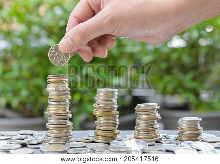 Woman hand putting coin to growing coins stacks with sun light - Concept of saving money