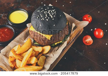 Black bun burger with potato wedges and sauces on wooden tray copy space. Appetizing cheeseburger with cutlet and tomatoes, fast food concept