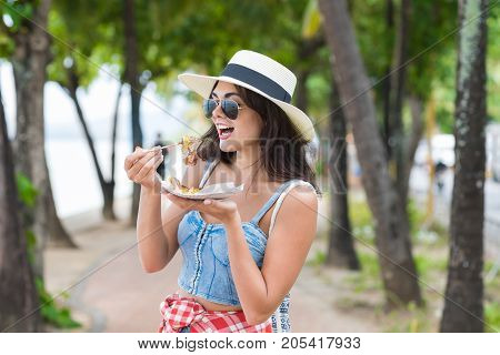 Beautiful Woman Eating Asian Street Food Walking In Park On Seaside Young Girl Tourist Try Exotic Meal During Vacation In Tropical Country