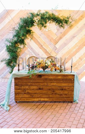 design, celebration, wedding concept. ravishing table for newlyweds decorated with light blue draping, wonderful bouquet of flowers, candles in elegant bronze holders