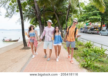 Happy Friends Walking Together In Park Near Sea Young Group Of People On Vacation Tourists Holiday And Communication Concept