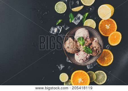 Portion of assorted ice cream scoops in bowl with ice cubes, lemon and orange slices and mint on black background top view. Delicious cold sweet dessert, copy space