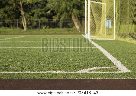 football field with artificial turf in the foreground with blurred background