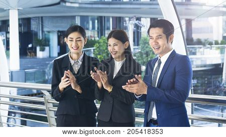 group of smart people of man and woman stand and clap hands in the feeling of happy and success at the outdoor pedestrian walk way