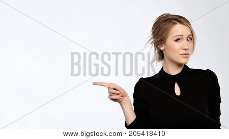 Frowning caucasian woman with disbelief thinking. Beautiful girl with make up pointing with finger aside