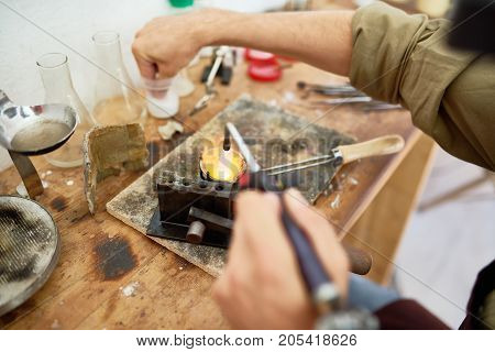 Closeup of male hands melting metal in cup while casting jewelry at workstation