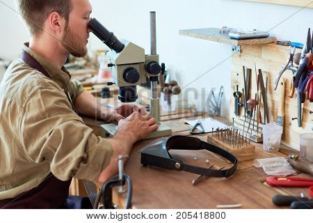 Side view portrait of young man inspecting precious stones using microscope sitting at workshop table