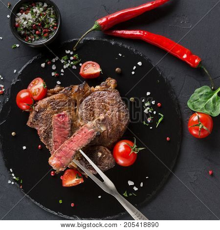 Rare rib eye steak on dark plate with meat fork decorated with tomatoes, chilli, spices, top view