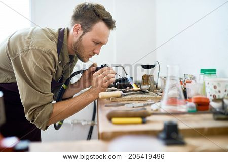 Side view portrait of  young man welding metal ring using gas torch in workshop
