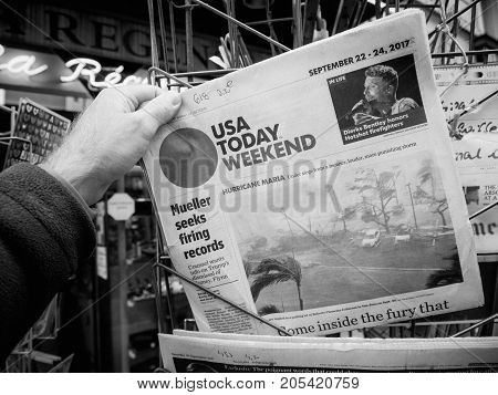 PARIS FRANCE - SEP 23 2017: Man buying latest newspaper USA TODAY with Hurricane Maria breaking news and picture of damages wind sea water