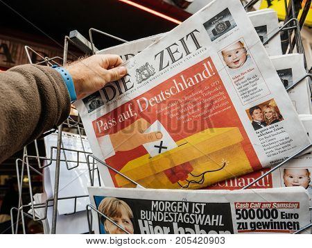 PARIS FRANCE - SEP 23 2017: Man buying latest newspaper Die Zeit German press with portrait of Angela Merkel before the election in Germany for the Chancellor of Germany the head of the federal government currently Angela Merkel