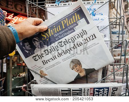 PARIS FRANCE - SEP 23 2017: Man buying latest The Daily Telegraph newspaper from press kiosk with Braking news from Theresa May British Prime Minister