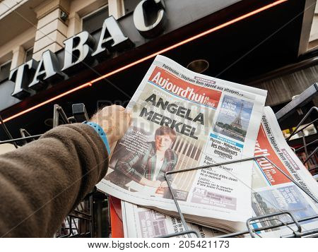 PARIS FRANCE - SEP 23 2017: Man buying latest French Aujord'hui newspaper with portrait of young Angela Merkel before the election in Germany for the Chancellor of Germany the head of the federal government currently Angela Merkel
