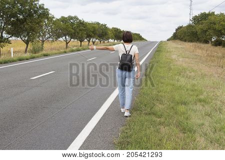 Hitchhiking the road. Female hand gesture,  road trip, travel. Young woman with a backpack hitch-hiking on a road at the fields. concept of people.
