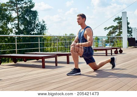 Sporty young man doing forward lunge and enjoying picturesque view while having workout on spacious terrace