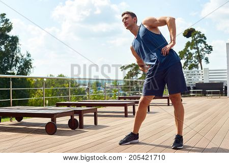 Full length portrait of handsome fit man doing stretching exercise and admiring picturesque view while having training at spacious terrace