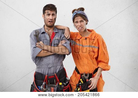 Discontent And Dissatisfied Woman And Man, Carpenters Look At Brocken Steps, Have Dirty Faces After