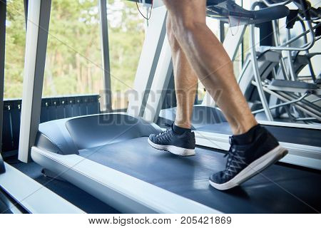 Close-up shot of unrecognizable sporty man running on treadmill in modern gym with panoramic windows