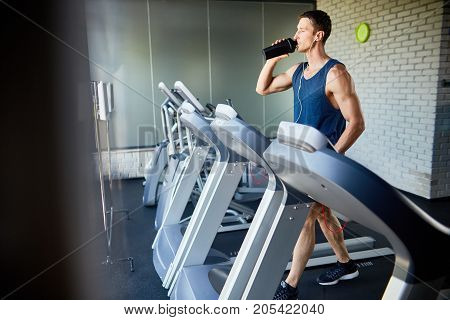 Young sportsman in headphones drinking water from bottle while running on treadmill in modern gym, profile view