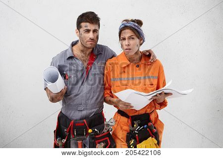 Talented Construction Workers Look Suspiciously At Camera, Hold Blueprint Or Sketch, Suspect That Th