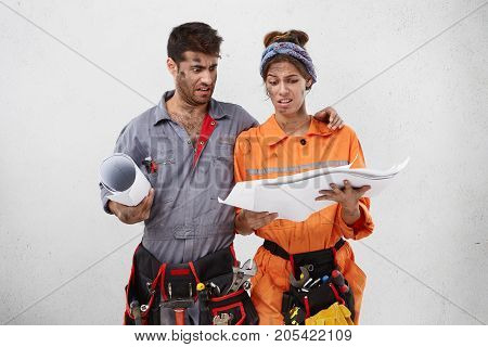 Professional Male And Female Industrial Workers Look With Discontent Expression At Blueprint, Try To