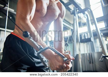 Close-up shot of unrecognizable muscular man with bare torso focused on training using cable crossover machine, interior of spacious gym on background