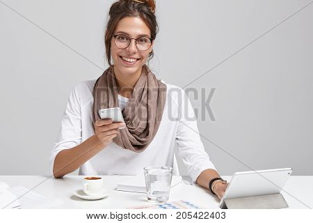 Horizontal Portrait Of Successful Smiling Female Office Worker Being Always In Touch, Works Simultan