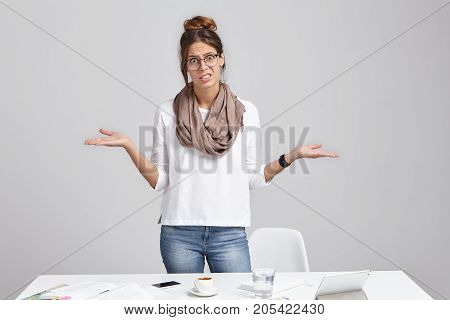 Unhappy Woman Frowns Face In Displaesure, Shrug Shoulders, Has Bad Mood, Stands At Office Table, Mak