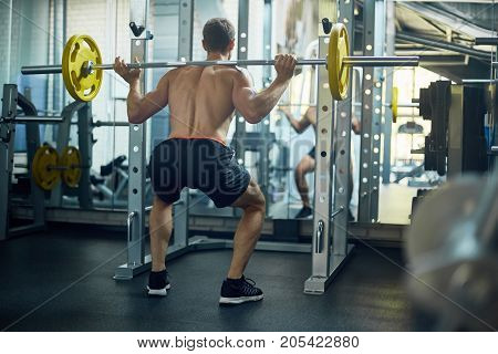 Back view of young bodybuilder flexing muscles with barbell in front of mirror while having intensive workout at gym