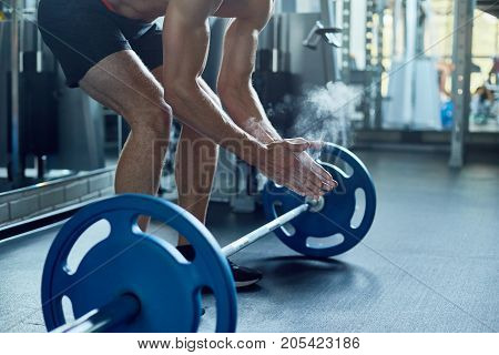 Unrecognizable young bodybuilder covering hands with chalk while preparing for lifting barbell at spacious gym