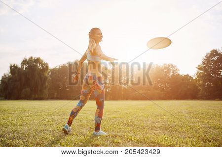 Young athletic girl playing with flying disc in the park. Professional player. Sport concept