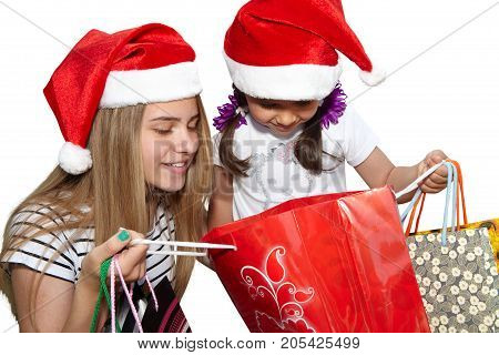 Two Little Girls In Fur-cap With Shopping Bags. Christmas