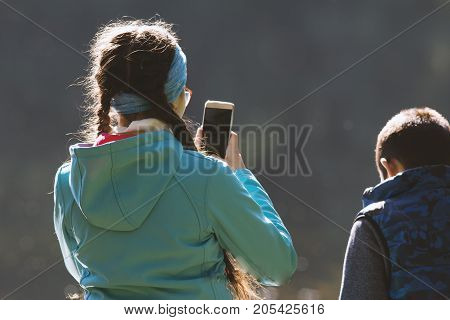 Young girl teenager taking picture by smartphone in the park, telephoto view