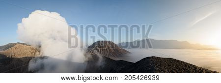 From the crest of Bromo's inner crater a panorama shows the sulphuric fumes Gunung Batok peak and a sea of clouds that run on the inner crater plain just before sunrise in Java Indonesia.