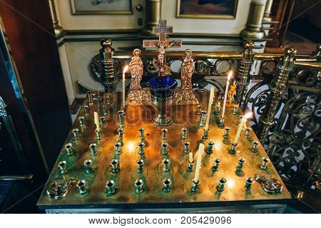 golden candleholder in church stand for candles in the interior of orthodox church orthodox icon lamp church oil church attribute symbolic gold cross with the crucifixion of Jesus