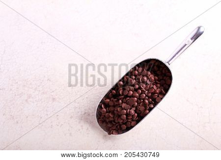Chocolate chips in metal scoop on marble table