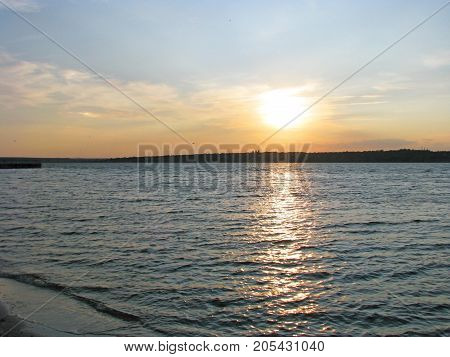 The sun sets over the horizon beautifully reflected in the river luminous path