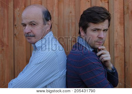 Father and son quarreled. They look with angry emotion at camera, arms crossed on their chests