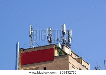 GSM transmitters on a roof of white administrative building. Close up .
